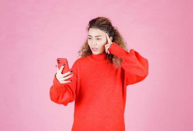 Vrouw die haar nieuwe berichten controleert en denkt.