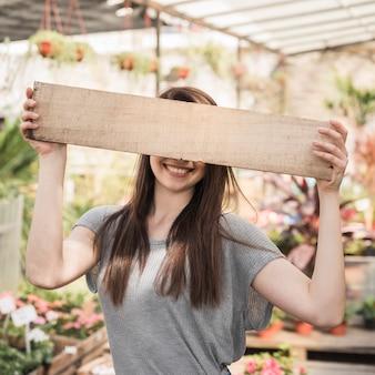 Vrouw die haar ogen achter houten plank verbergt