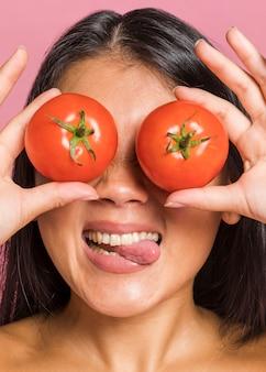 Vrouw die haar ogen behandelt en tong uitsteekt