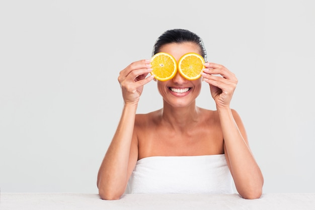 Vrouw die haar ogen behandelt met stukjes sinaasappel