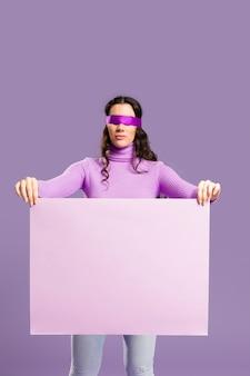 Vrouw die haar ogen heeft gebonden die een leeg karton houden