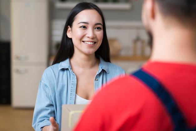 Vrouw die haar online bestelling van de bezorger ontvangt