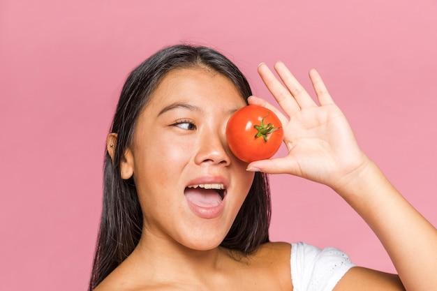 Vrouw die haar oog behandelt met tomaat