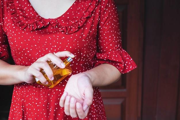 Vrouw die haar parfumfles bespuit