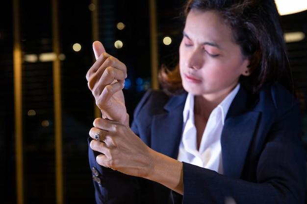Vrouw die haar polspijn van het gebruiken van computer houdt. office-syndroom concept