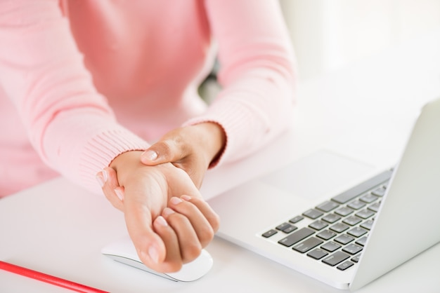Vrouw die haar polspijn van het gebruiken van computer houdt. office-syndroom