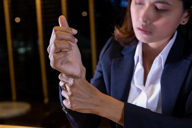Vrouw die haar polspijn van het gebruiken van computer houdt.
