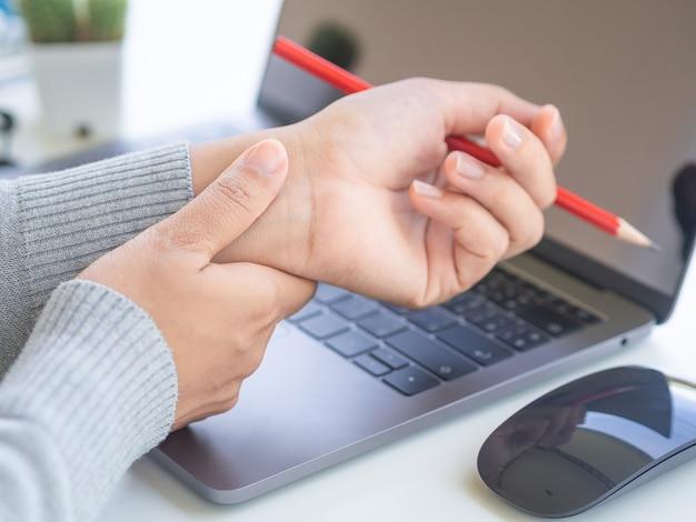Vrouw die haar polspijn van het gebruiken van oude computer houdt.