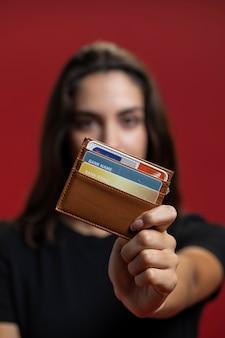 Vrouw die haar portefeuilleclose-up steunt