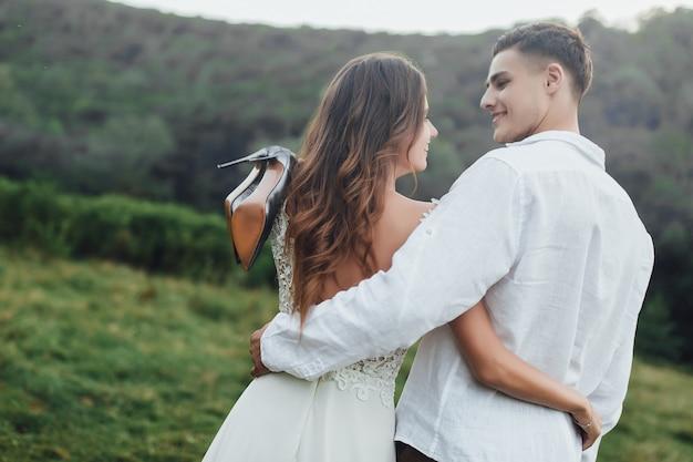 Vrouw die haar schoenen op hand houdt. echtpaar op landschap! levensstijl