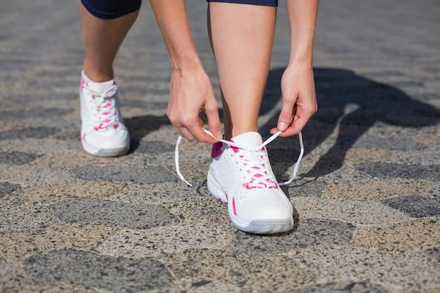 Vrouw die haar schoenveter vastbindt op loopschoen