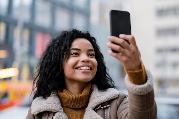 Vrouw die haar smartphone buiten bekijkt