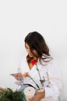 Vrouw die haar smartphone buitenshuis gebruikt terwijl ze koffie drinkt