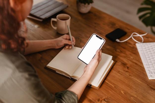 Vrouw die haar smartphone gebruikt en in agenda opschrijft