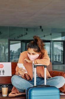 Vrouw die haar smartphone gebruikt op de luchthaven terwijl ze op haar bagage leunt tijdens een pandemie