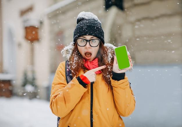 Vrouw die haar smartphone in de winterstraat richt