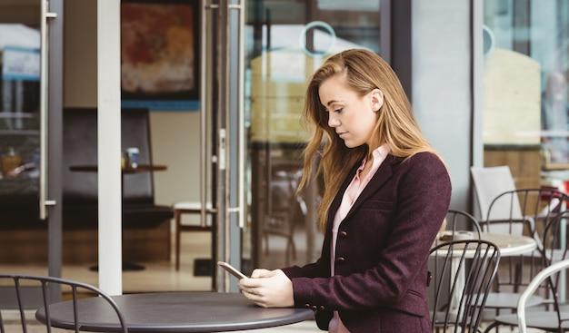 Vrouw die haar smartphone in koffie gebruikt