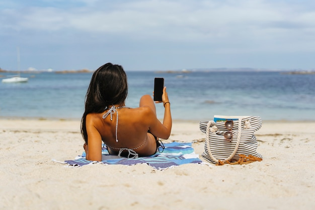 Vrouw die haar smartphone mobiel in het zand in het strand gebruiken