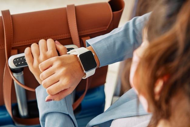 Vrouw die haar smartwatch bekijkt terwijl op de luchthaven tijdens pandemie