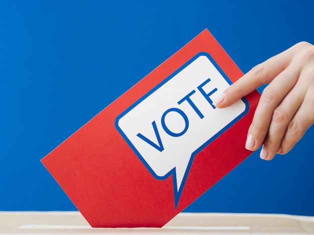 Vrouw die haar stemming plaatst in de verkiezingsdoos