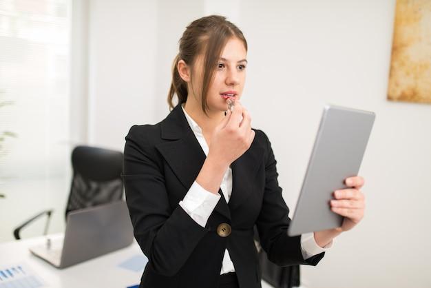 Vrouw die haar tablet gebruiken als spiegel om op wat lippenstift in het bureau te zetten