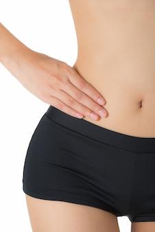 Vrouw die haar taille houdt en op lage rugpijngebied masseert dat op witte achtergrond wordt geïsoleerd