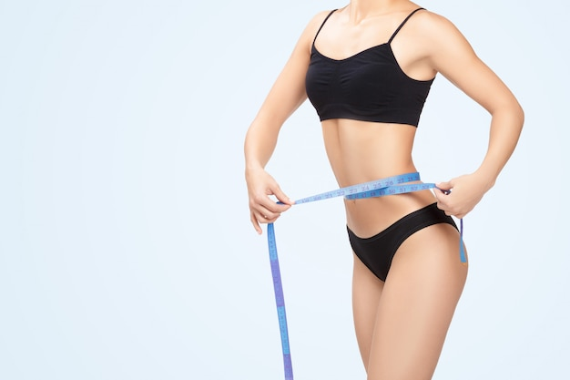 Vrouw die haar taille meet door blauwe maatregelenband