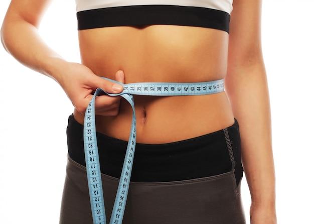 Vrouw die haar taille meet. perfect slank lichaam. geïsoleerd op wit.