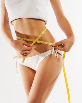 Vrouw die haar taille meet. perfect slank lichaam