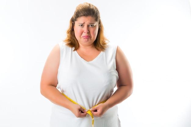 Vrouw die haar taille met band meet