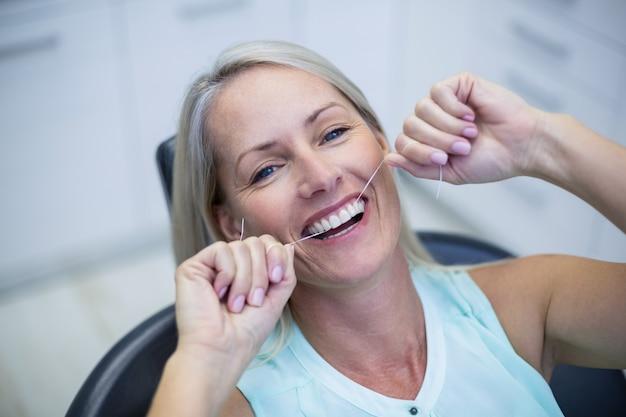 Vrouw die haar tanden flossen