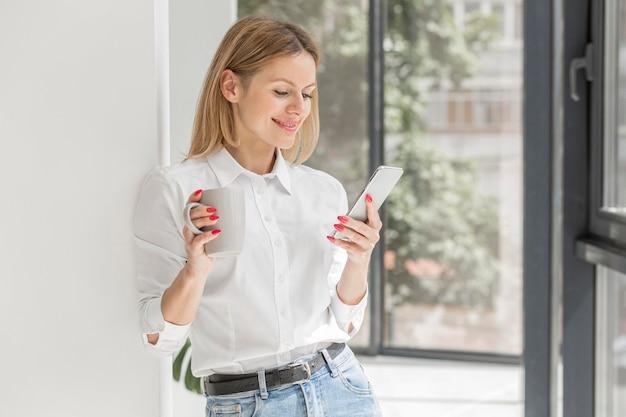 Vrouw die haar telefoon binnen bekijkt