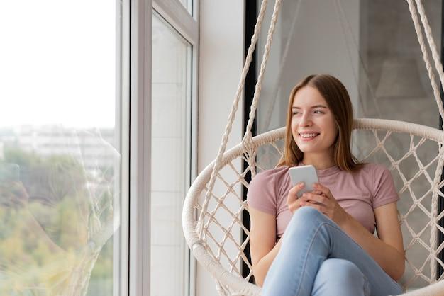 Vrouw die haar telefoon controleert en op het venster kijkt