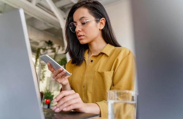 Vrouw die haar telefoon controleert terwijl u werkt