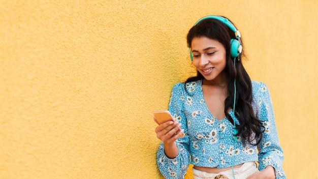 Vrouw die haar telefoon en glimlach met exemplaarruimte bekijkt