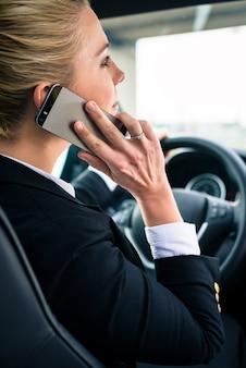 Vrouw die haar telefoon met behulp van terwijl het drijven van de auto