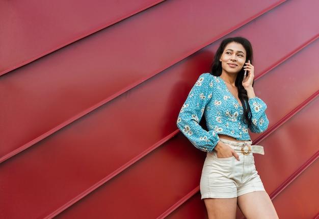 Vrouw die haar telefoon met rode tinachtergrond met behulp van