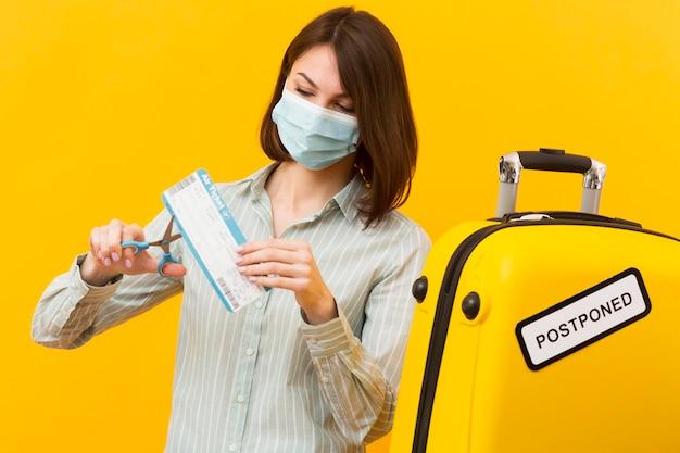 Vrouw die haar vliegtuigticket snijdt