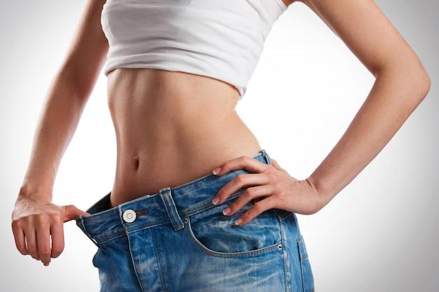 Vrouw die haar vooruitgang na gewichtsverlies toont
