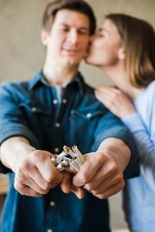 Vrouw die haar vriend gebroken bundel van sigaretten kust