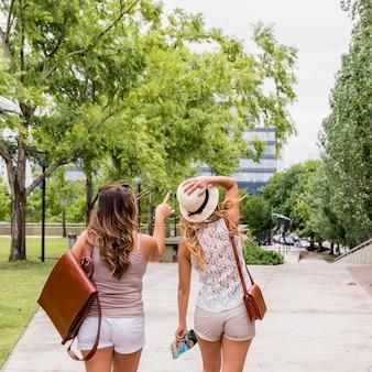 Vrouw die haar vrouwelijke vriend bekijkt die op iets in het park richt