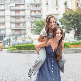 Vrouw die haar vrouwelijke vriend op rugrit neemt bij straat