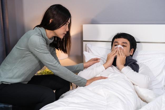 Vrouw die haar zieke echtgenoot bezoekt en verzorgt terwijl hij thuis op bed ligt