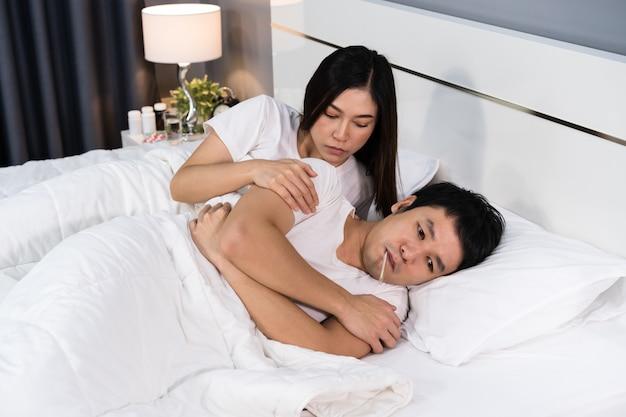 Vrouw die haar zieke echtgenoot op bed thuis behandelen