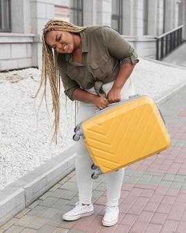 Vrouw die haar zware bagage probeert op te tillen