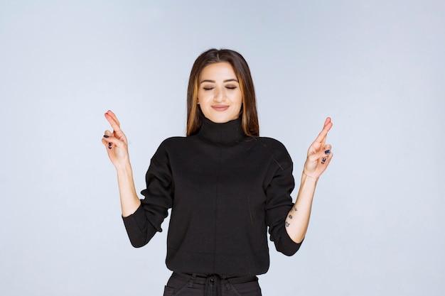 Vrouw die hand kruisteken toont.