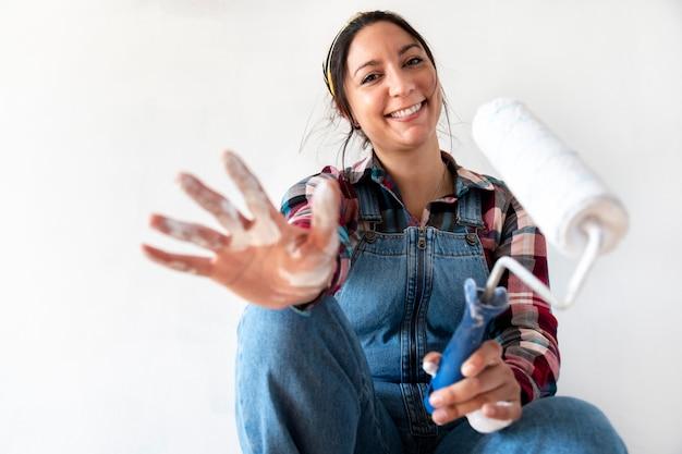 Vrouw die hand met verf toont die camera bekijkt verfroller vasthoudt selectieve focus op gezicht