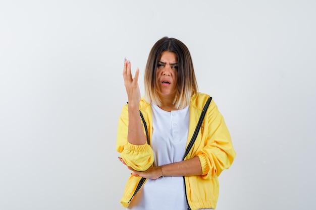 Vrouw die hand op vragende manier in t-shirt, jasje opheft en verbaasd kijkt. vooraanzicht.