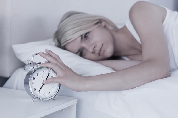 Vrouw die hand uitbreidt aan wekker in bed