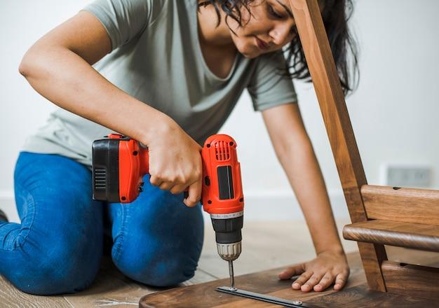 Vrouw die handboor gebruiken om een houten lijst te assembleren